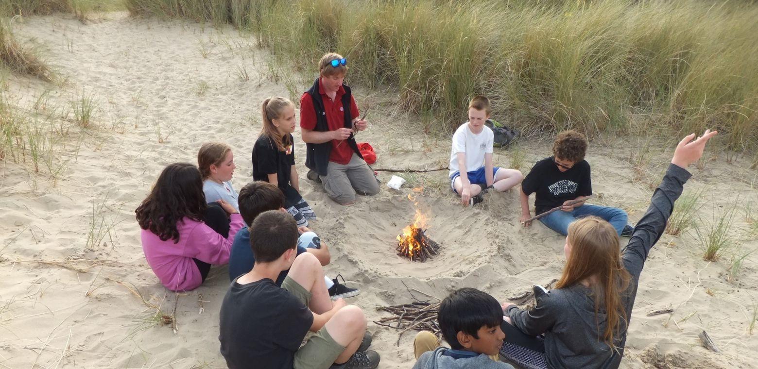 children sitting around a fire