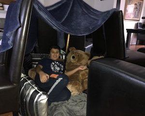 boy and bear in den