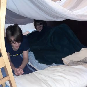 two children in a den made of blankets