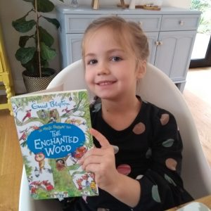 little girl holding the enchanted wood book
