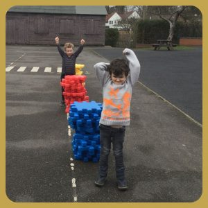 school children playing with giant building blocks in playground