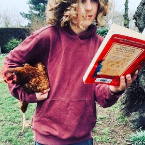 girl holding chicken reading a book