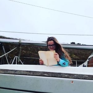 girl reading book on boat