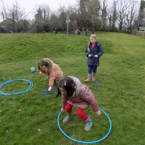 school children playing outside on grass with hula hoops and rope
