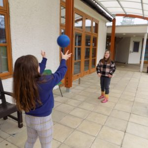 two girls playing catch with a blue ball
