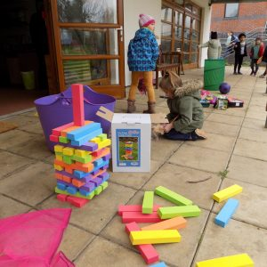 school children building a giant rainbow jenga tower outside