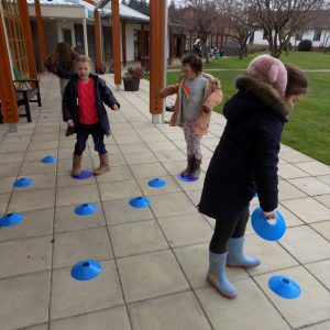 school children setting up a game outside using blue markers