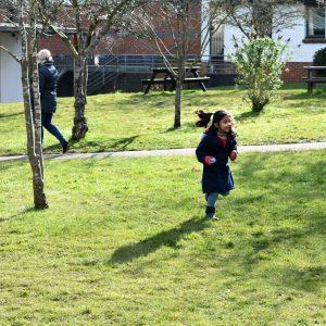 school girl running across grass holding easter egg
