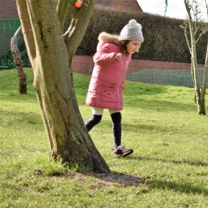 school girl playing by trees