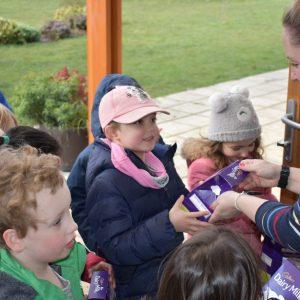 teacher giving children Easter eggs