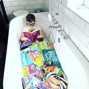 child in bath with books