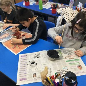 school pupils painting pottery