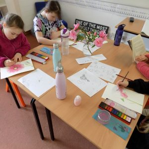 girls at a classroom desk painting drawing and reading