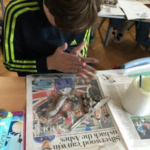 school boy making clay model in art class