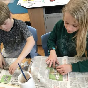 boy and girl making clay models in art class