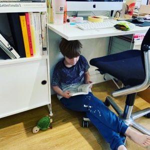 child reading under desk
