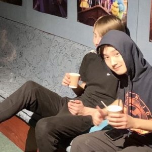 teenage students in hoodies with hot drinks