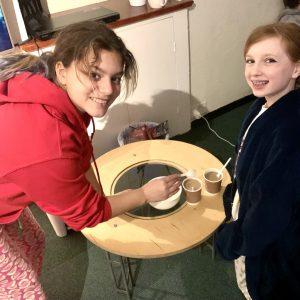 school children in nightwear making hot chocolate