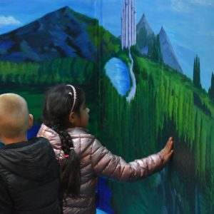 school children looking at new mural painted on wall