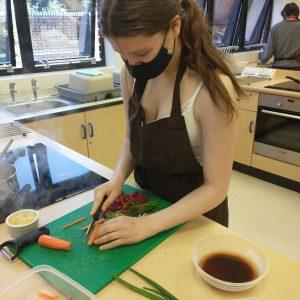 teenage girl chopping vegetables