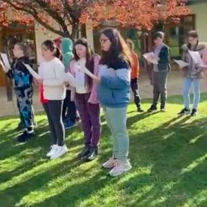 school children singing outdoors