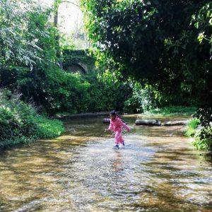 girl paddling in a stream