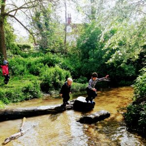 two boys jumping across stepping stones on a stream