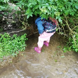 child in welly boots walking in a stream