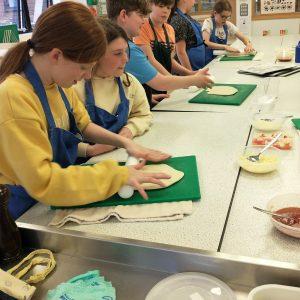 school children rolling out pizzas