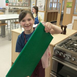 child holding a green chopping board