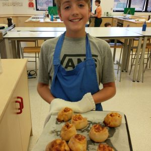 boy holding tray of cooked Pizza Pinwheels