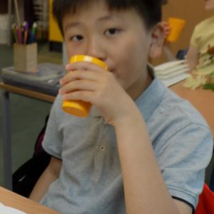 boy drinking from yellow cup