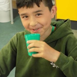 child drinking from a green cup