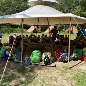school children sitting under a camping canopy