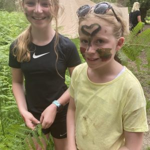 children with face paint in woodland