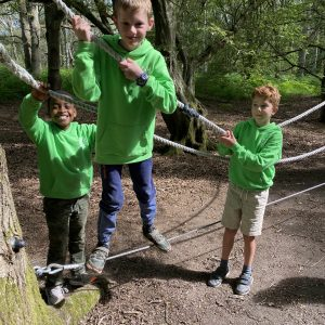 3 boys wearing bright green hoodies on a rope obstacle course