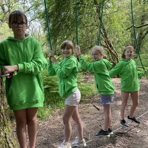 four girls on tightrope in wood