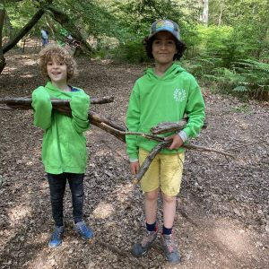 2 children wearing bright green hoodies holding a pile of large branches