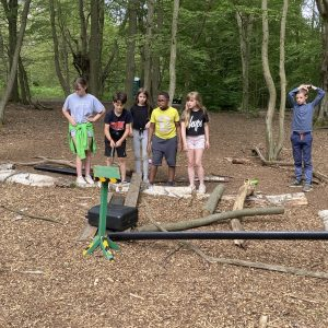 A group of children in the woods trying out obstacle courses
