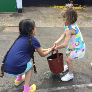 two girls carrying buckets of water