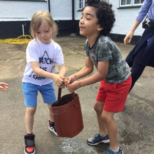 two children carrying a bucket of water