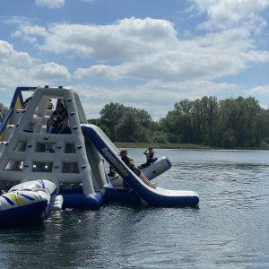 children on inflatable play equipment on lake