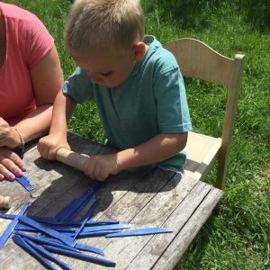 child using rolling pin outdoors
