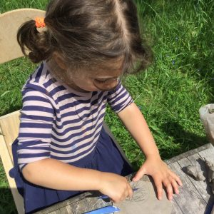 girl using clay outdoors